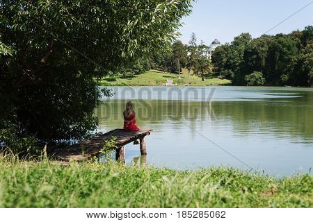 Blonde girl is sitting on a wooden pier. Summer vacation in a green park by the pond. Sunny weather