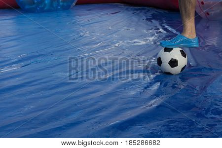 Zorb ball football game Field with Men leg on the ball.