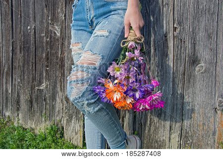 teenage girl with colorful daisy bouquet and frayed blue jeans by rustic barn