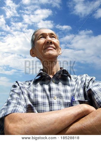 Isolated chinese senior man with confident and cloudy blue sky