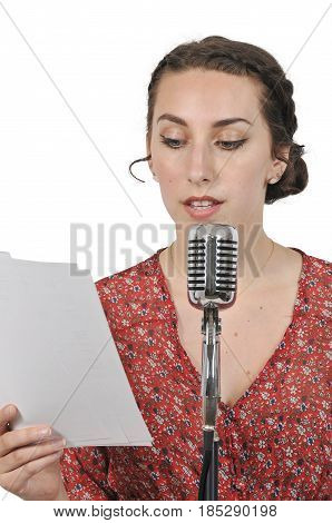 Woman speaking into a vintage microphone performing a radio play