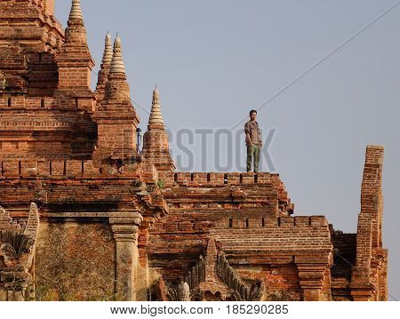 Bagan, Myanmar - Oct 3, 2015. A tourist standing on top of Buddhist temple in Bagan Myanmar. Bagan is one of the world greatest archeological sites a sight to rival Machu Picchu or Angkor Wat.