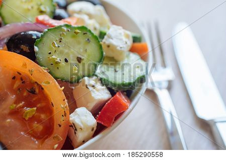 Greek salad with feta cheese black olives tomato cucumber and onion. Selective focus flatware on background