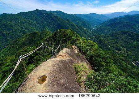 Dangerous hiking trail along a narrow and rocky mountain ridge at Wu Liao Jian in Taiwan