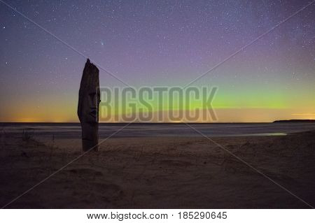 Wooden statue of idol on sandy coast against starry sky with northern lights