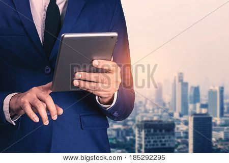 Young businessman with a tablet in town of society.
