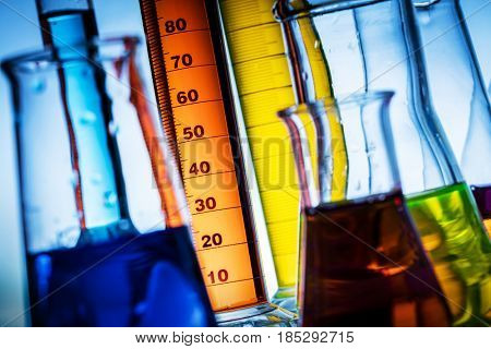 Laboratory glass filled with colorful substances. Chemical liquid measurement and analysis.