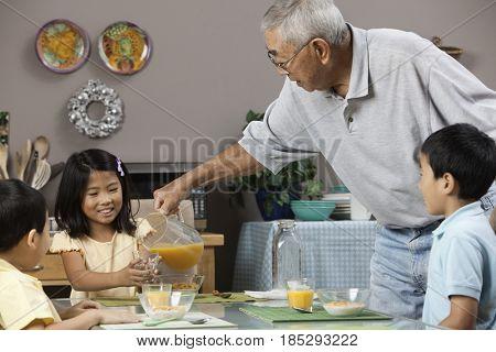 Asian grandfather serving grandchildren orange juice
