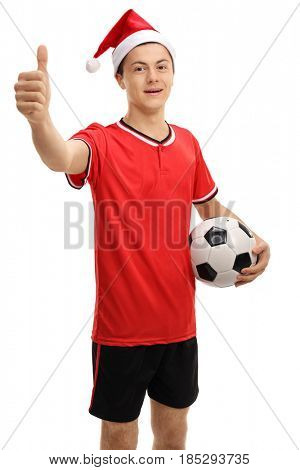 Teenage soccer player with a christmas hat making a thumb up sign isolated on white background