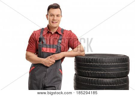 Mechanic leaning on a stack of tires and looking at the camera isolated on white background