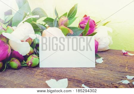 Peony background. Fuchsia pink and white peonies on old wooden table with an empty card for text. Happy Mothers Day. Mother's greetings card. Valentines. Copy space.