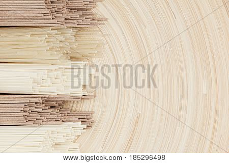 Bundles of raw chinece noodles on soft beige wooden board with copy space top view.
