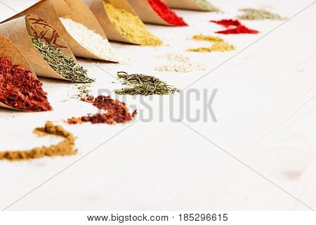 Oriental colorful powder condiments pattern as decorative border on white wooden board with copy space.