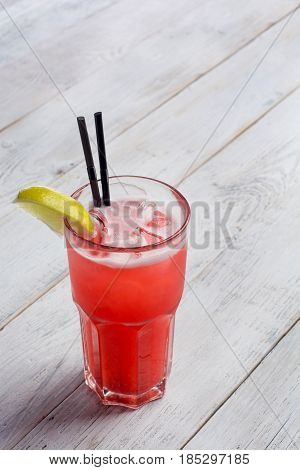 red limonade in glass on white wooden background.