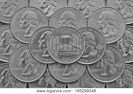 Arkansas State and coins of USA. Pile of the US quarter coins with George Washington and on the top a quarter of Arkansas State.