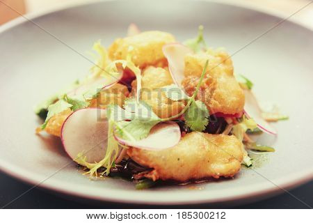 Fish tempura with cilantro herb in grey porcelain plate, close-up, toned image