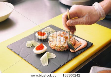 Chef is decorating crab salad with sauce in restaurant kitchen, toned image