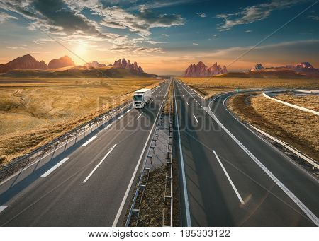 Single delivery truck driving from the mountain range towards the setting sun. Fast motion drive on the straight freeway in beautiful landscape. Freight scene on the empty motorway.