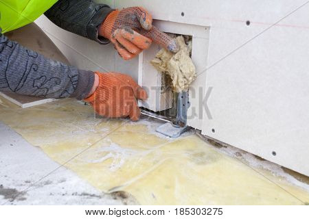 Construction worker clamps wall mount with wrench