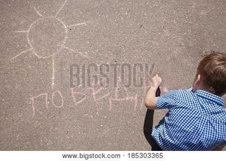 Top view on kid boy drawing and writing word Victory in Russian on asphalt. May 9th. Victory day in Russia. Peace in the world. Memorial day