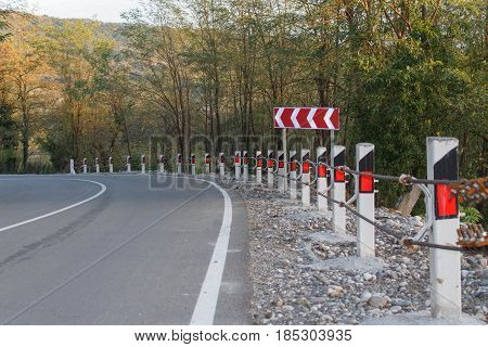 Road fence barrier. Canyon road with prominent tree and nice evening sky. Traffic Barrier safety road on road. Close up asphalt road texture with white stripe