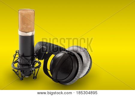 Headphones and condenser microphone on the yellow background.