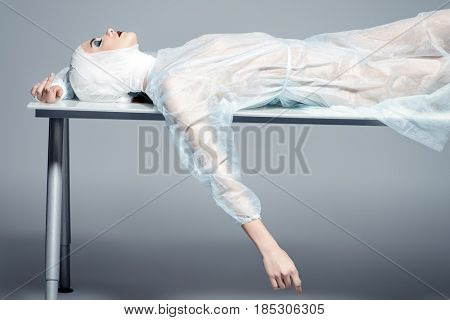 Beauty, fashion and medicine, plastic surgery. Portrait of an attractive young woman in bandages and hospital gown lying on the operating table.