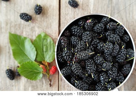 black mulberry berries in a pot on a wooden table. in the foreground are mulberry berries and sprig with ripened berries.