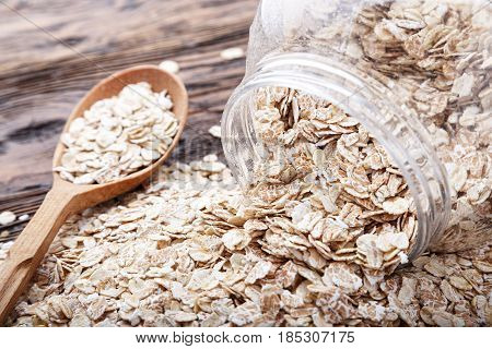 Inverted can of oatmeal on a wooden table. The oatmeal is scattered on the table and in a wooden spoon. Healthy food for breakfast