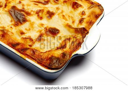 Lasagna in baking dish isolated on white bacground