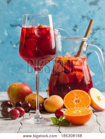 Refreshing sangria or punch with fruits in glass and pincher