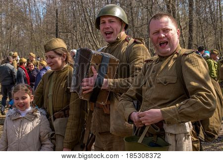 Gatchina, Russia - May 7, 2017: Historical reconstruction of the battles of World War II. Soldiers sing the song of the war - Katyusha. The soldier plays the accordion.