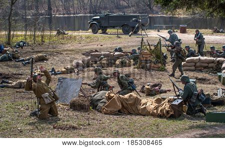 Gatchina, Russia - May 7, 2017: Historical reconstruction of the battles of World War II. German soldiers defend a mortar battery. The dead Soviet soldier falls.
