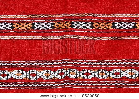 Red ethnographical handmade blanket with color pattern.