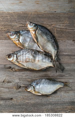 Four salted fish, dried and ready to eat, lying on the old wooden table, topview