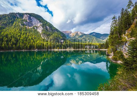The concept of walking and eco-tourism. South Tyrol, Italy. Magnificent lake Lago di Braies. Emerald expanse of water reflects the surrounding forest and mountains
