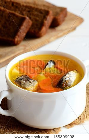 Easy and tasty fish soup recipe. Healthy fish soup with potatoes and carrots in a bowl. Rye bread pieces on white wooden table. Vertical photo. Closeup