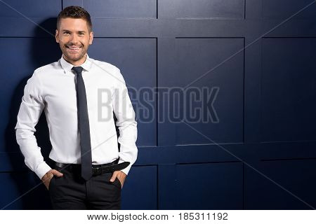 Portrait of style. Smiling successful man looking at camera with glee. His hands in the pockets of his pants. Copy space in the right side