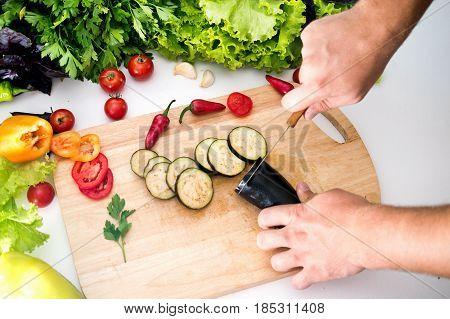 A man prepares a dinner of vegetables, cuts eggplants, tomatoes, peppers, lettuce, greens. Useful vegetarian food