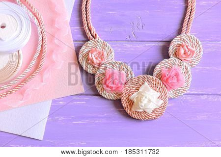 Beautiful necklace for women. Women's necklace created of ribbons, cords and felt. Materials to create accessory on a wooden table. Floral summer jewelry. Top view