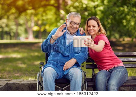 cheerful daughter with her disabled father in wheelchair using a digital tablet, talking and smiling while spending time in the park