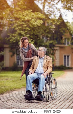 Medical: Happy caregiver daughter with senior man in wheelchair