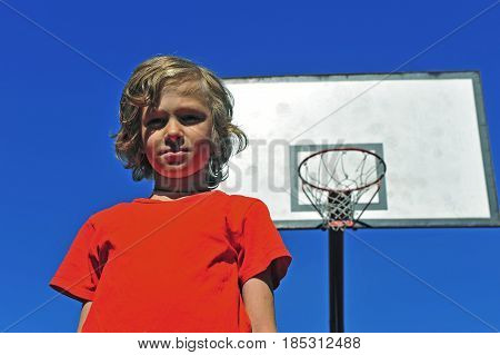 Boy in red t-shirt with basketball hoop on background