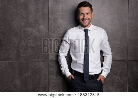 Wealthy and happy. Smiling young businessman standing and looking at camera with joy. His hands in the pockets of his pants. Copy space in the left side