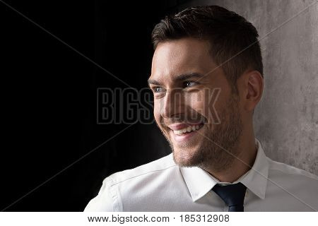 Think, live and be positive. Portrait of noble young businessman with stubble laughing. Man is looking aside with anticipation. Copy space in the left side