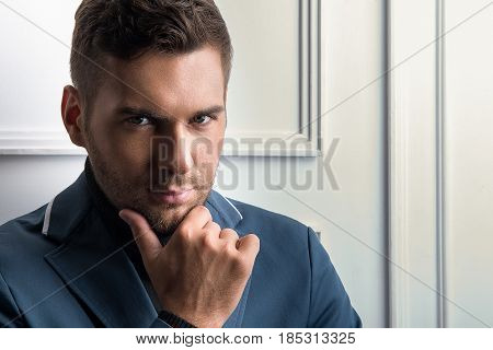Seductive look. Portrait of fashion classy young man looking at camera seriously. He touching his chin