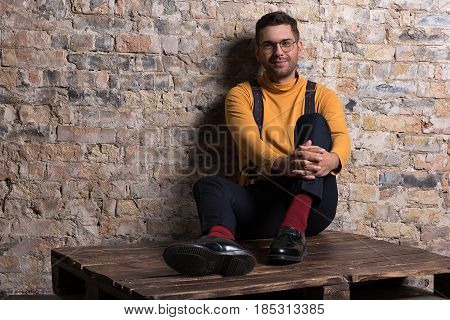 Be yourself. Stylish young guy sitting on wooden pallet. He holding his knee while looking at camera with smile against brick wall