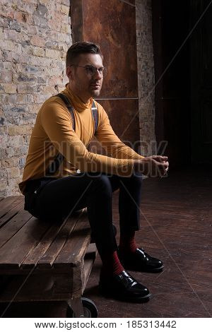 Expectation. Serious young male looking aside with anticipation. He sitting on wooden pallet, arms on knees against brick wall