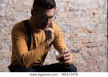 Drowning sorrows in alcohol. Sad young man sitting with glass and thinking. He looking at bottom of glass and touching his chin