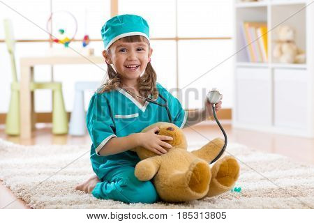 Happy kid little doctor girl examines teddy bear in nursery room at home